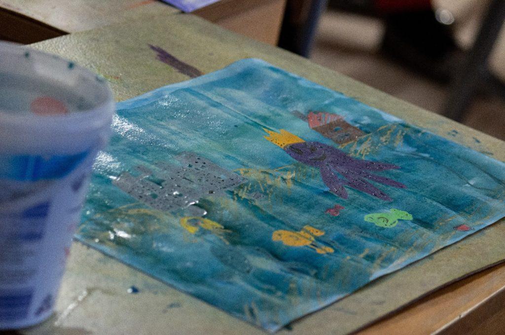 Koululaisen Uponnut kaupunki -aiheinen piirustus, jossa mustekala ja kaloja