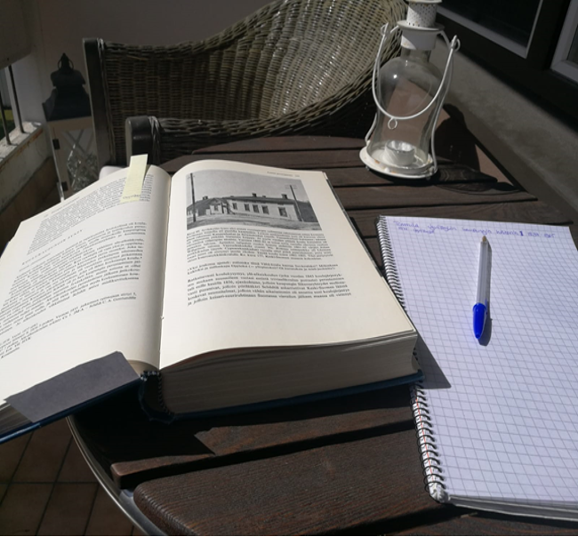 Parvekkeen pöydällä avonainen kirja, muistiinpanolehtiö ja kynä.