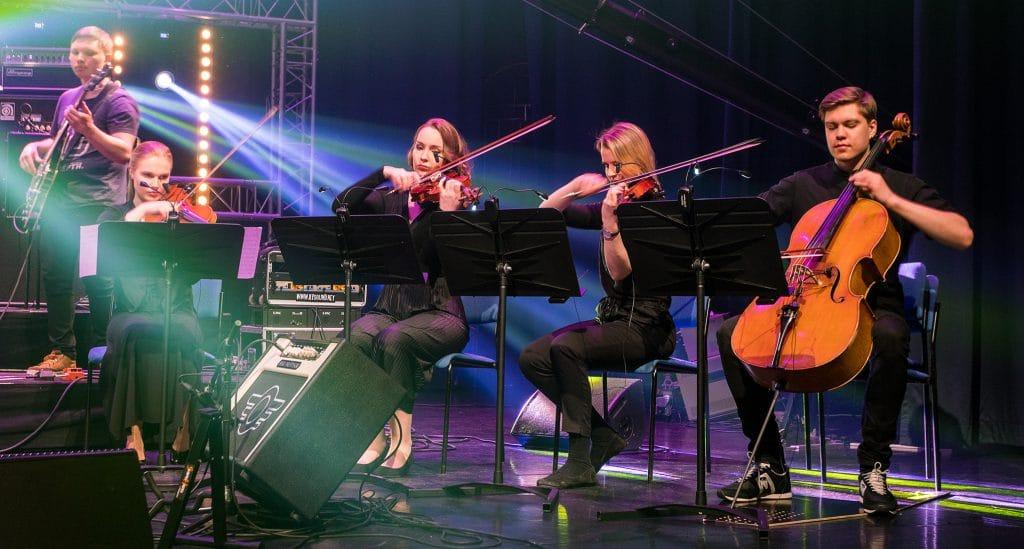Basisti ja jousikvartetti esiintymässä Siltasalissa show-valoissa