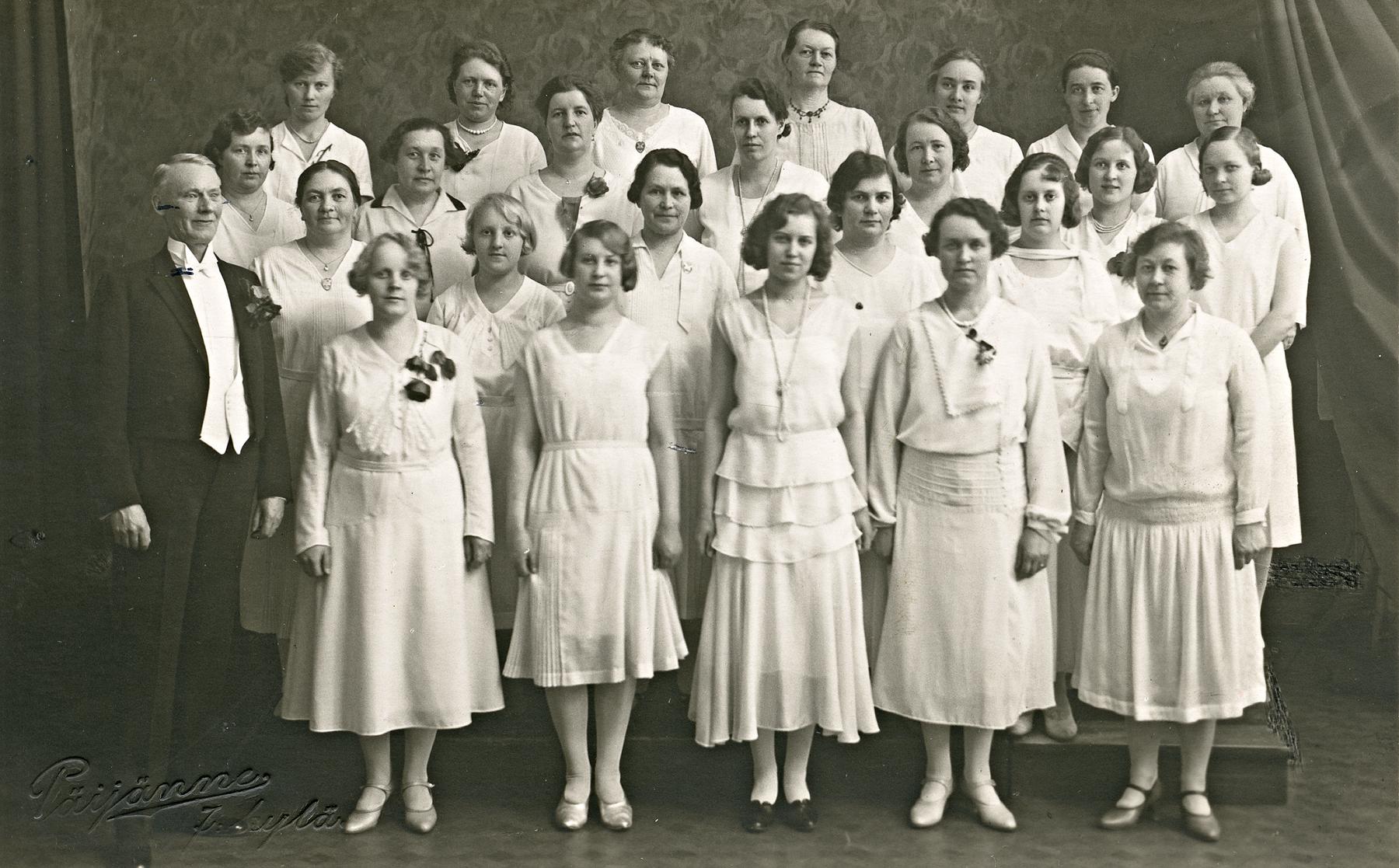 Mustavalkokuva naiskuoro Vapuista valkoisissa vaatteissa