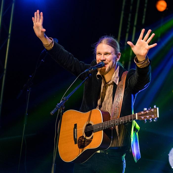 Kitaristi-laulaja kiittää yleisöä kädet ilmassa