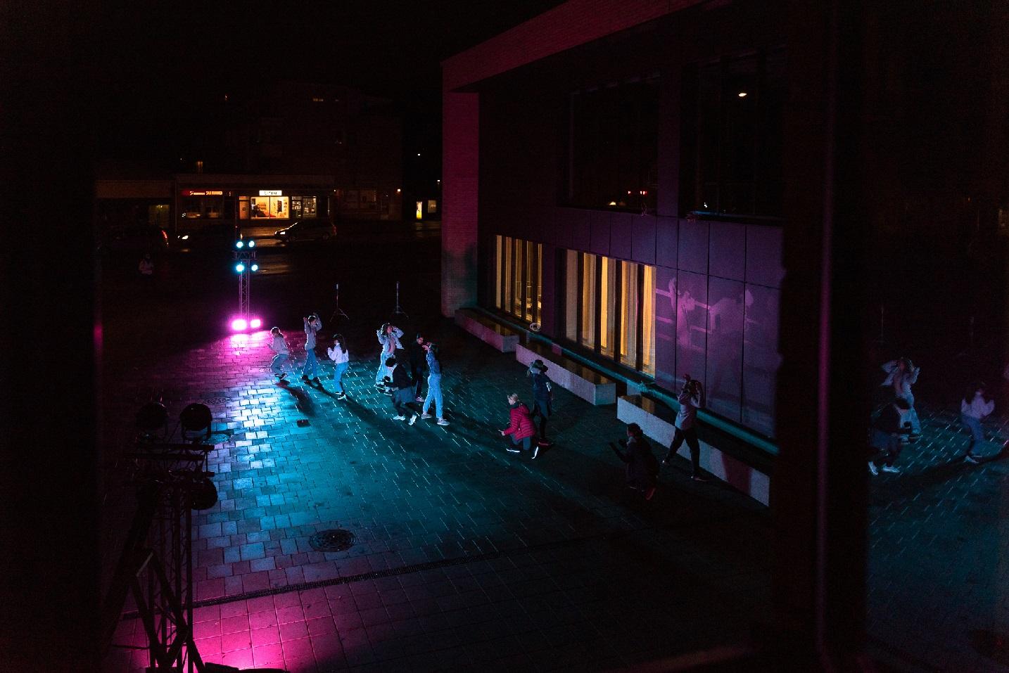 Tanssijoita Musiikkikampuksen etuoven edessä sinisessä ja violetissa valossa.